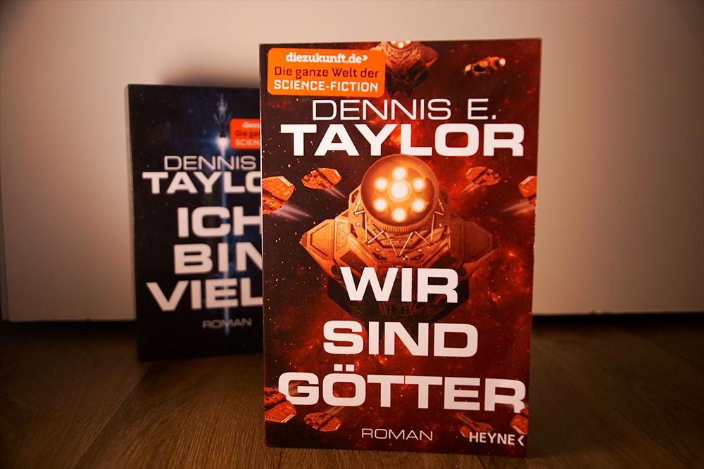 Das Buchcover von Wir sind Götter von Dennis E. Taylor. Im Hintergrund Band 1, Ich bin viele von Dennis E. Taylor - Foto: Kia Kahawa